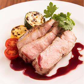 [写真]赤ワインソースをかけた厚切りポークステーキ